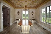 The dining room offers a view of the property on two sides, with tumbled marble floors, Italian gold leaf motif on ceiling and antique Mexican sconces.