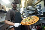Gary Holt shows off a freshly baked pizza at Rocky's Pizza & Panini on Bardstown Road.