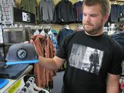 "Dan, an employee at the Heritage Surf Shop, displays a ""Restore the Core"" fundraiser hat."