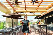 Allie Quade, server at Hi Jax, serves drinks at the rooftop restaurant at Jax Fish House & Oyster Bar in CitySet.