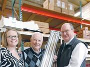 The family members behind Pacific Lamp and Supply Co. are, from left, General Manager Shannon Carr, President John Albert Kelly and Mark Reynolds, who recently retired as vice president. They're holding a T5 Vapor Tight fluorescent light fixture.