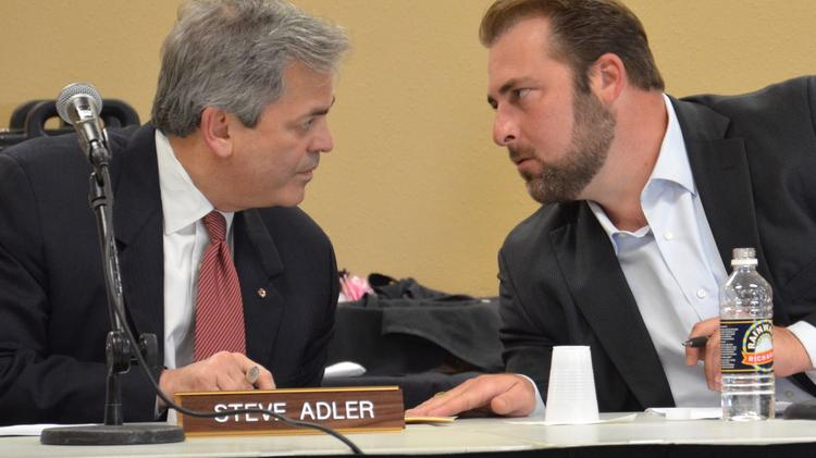 Austin Mayor Steve Adler, left, and Hays County Commissioner Will Conley, both members of the CAMPO policy board, discuss Monday night Adler's proposed amendments to a resolution that all but kills Lone Star Rail. The resolution passed nearly unanimously.