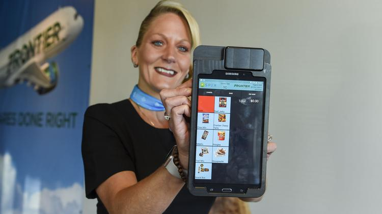 Frontier flight attendant Stefanie Coppedge shows off Samsung's Fly Tab tablet, which has increased on-board sales.