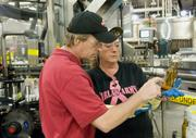 Out on the floor, Lee checks a bottle with Karla Behmer after it had gone through a new labeling machine.
