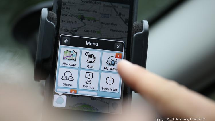 An automobile driver uses the Waze Inc.'s mapping service, displayed on an Apple Inc. iPhone 5. Photographer: Chris Ratcliffe/Bloomberg