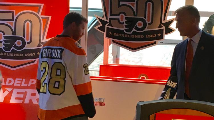 798a343ec47 ... norway flyers captain claude giroux tries on the teams 50th anniversary  jersey as flyers president paul