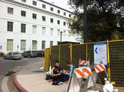 Students take the work in stride, studying on the curb outside the construction site.