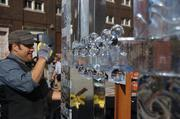 A sculptor puts the finishing touches on the ice sculpture, even as the hot afternoon sun melted the piece of art.