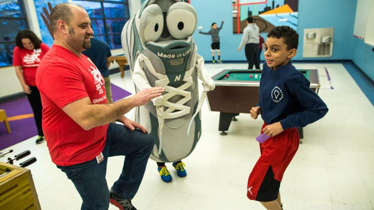 """New Balance Retail District Manager Jay Rowe, New Balance mascot """"Newbie"""" and club member Marley Forbes practice """"high knees"""" as part of New Balance Kids in Motion program that combats childhood obesity and promotes healthy lifestyles at West End House Boys and Girls Club."""