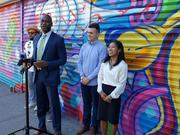 Pictured (at the microphone): Gregg Bishop, N.Y.C.'s Commissioner of Small Business Services standing outside Katz Deli on the Lower East Side of Manhattan commemorating the last mural to be painted as part of the 100 Gates Project, which began in 2014. To his right is artist L'Amour Supreme, and to his left Tim Laughlin, executive director of the Lower East Side Business Improvement District, and EDC president Maria Torres-Springer.