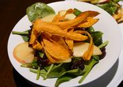 The grilled chicken apple harvest salad features a garnish of sweet potato crisps.