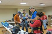 Over the Edge staging manager Mike Hills (left) helps members of the local media into their harnesses and helmets.