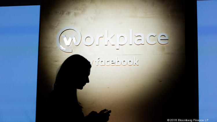 "An attendee uses a mobile phone in front of the Workplace by Facebook logo during the global launch event of ""Workplace"" at the Facebook Inc. Workplace is meant to help employees collaborate with one another on products, listen to their bosses speak on Facebook Live and post updates on their work in the News Feed. Photographer: Jason Alden/Bloomberg"