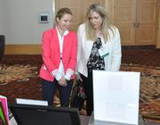 Ksenia Khutorova with Alpert Enterprises and honoree Claudine Claus of Home Financing Center looking at the offerings for the silent auction.