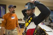 Jason McDowell of OnMilwaukee.com is getting prepped by Over the Edge employee Mike Hills in preparation for his turn.