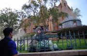 Madame Carlotta, one of the Haunted Mansion's 999 happy haunts, sits on the lawn and chats with guests in the line.