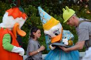 Speaking of ducks, Taylor Edmondson and her dad, Michael, get autographs from a costumed Donald and Daisy Duck.