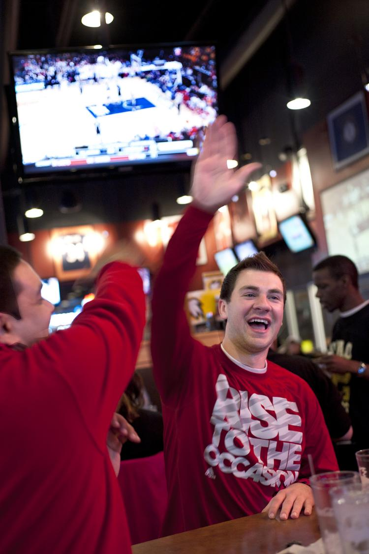 Aldin Zukanovic, right, high-fived Kush Patel, left, after a play during the Louisville- Villanova game they watched at the Buffalo Wild Wings in  Shelbyville Road Plaza.