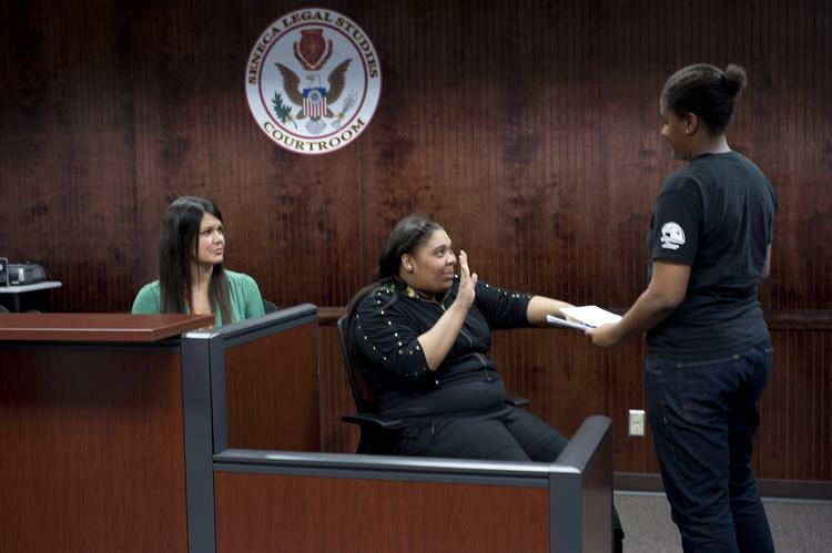 Antwanazia Henry, sophomore, acted as a witness and lifted her right hand and swore to tell the truth during a mock trial in Seneca High Schools simulated courtroom. Keaira Pennie, senior, played the bailiff, right, while teacher Emily Fritts, far left, sat in as judge.