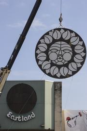 """The final """"Rising Sun"""" sign at Eastland Mall being removed and prepared for transport to a storage facility in Concord as it awaits future installation as public art."""