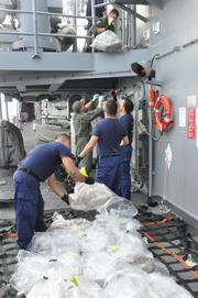 Personnel from the U.S. Coast Guard Law Enforcement detachment embarked aboard the guided-missile frigate USS Rentz (FFG 46) prepare an estimated $78 million of confiscated cocaine for transfer to the U.S Coast Guard cutter USCGC Forward (WMEC 911). The drugs were confiscated from a drug bust made on Aug. 16 during Operation Martillo counter transnational organized crime operations while assigned to U.S. 4th Fleet. (U.S. Navy photo by Lt. Cmdr. Corey Barker/Released)