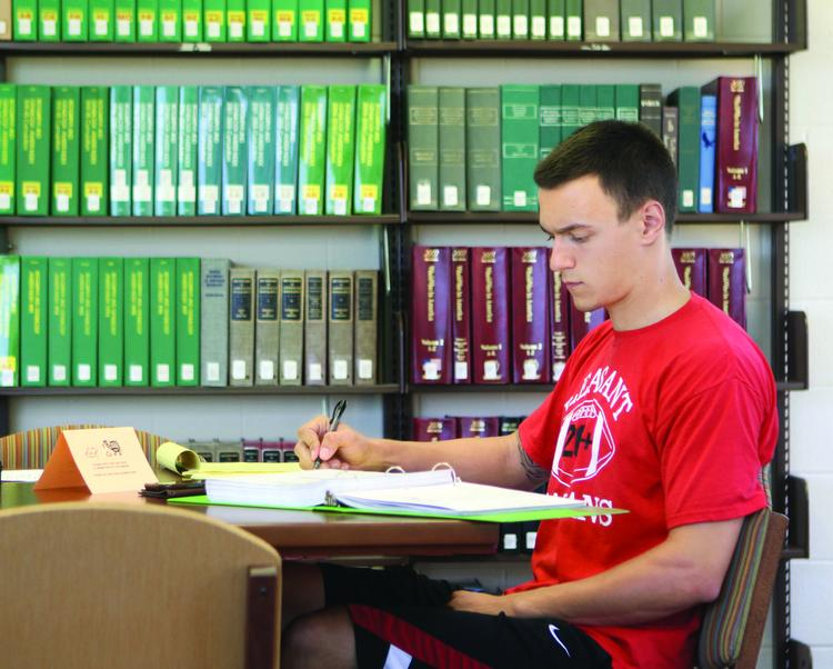 Dan Lee, a junior finance and English major at Robert Morris University, studies with a finance textbook borrowed from the library's textbook reserve program. Lee said that he purchased only two textbooks this semester and that by borrowing two others through the program, he is saving about $250.