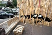 """Some of the pallets were used to make benches and a table in front of Greg Lewis' exterior art installation """"Boxed Up"""" at the old Chutney's restaurant on 15th Avenue East on Seattle's Capitol Hill."""