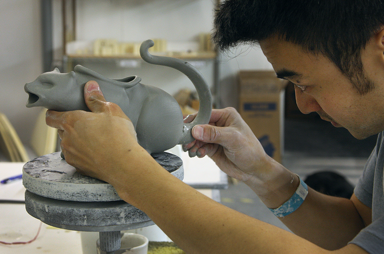 "Daniel Granias works on a Puking Kitty Saucy Boat. Granias is a graduate of the Oregon College and Craft, where his focus was ceramics ""Only in Portland could you find a job in ceramics after getting a degree in Art,"" he said."