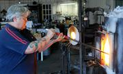 Girl Glass Studio owner and artist Shannon Jane Morgan gathers glass. There are 75 pounds of molten glass in the crucible.