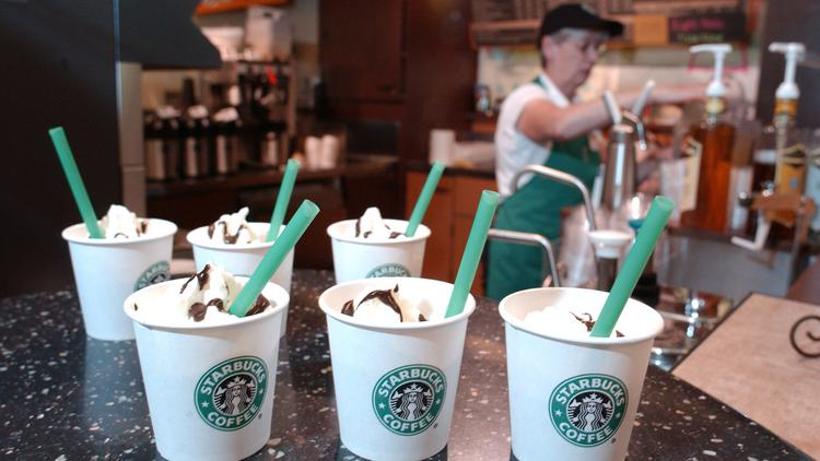 A Starbucks employee works behind the counter.