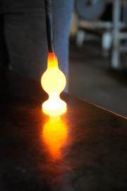 A goblet is formed by letting the molten glass pool on the marvering table.
