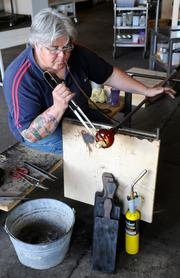 Girl Glass Studio owner Shannon Jane Morgan shapes a goblet with tweezers and wet newspapers.