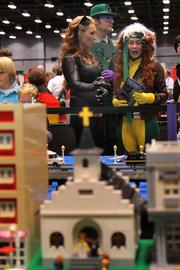Costumed fans look at the model Lego town.