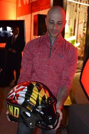 Adam Clement, Under Armour's creative director of team sports, displays one of 200 hand-painted Maryland football helmets featuring a waving Maryland flag.