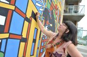A silhouette of Reston founder Robert E. Simon overlooks Deborah Brehony as she puts some finishing touches on a mural created by Artist Dana Scheurer. The mural will be dedicated this Saturday, Sept. 21, at the Midtown Mural ribbon cutting in Reston.