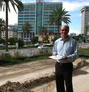 Alex Coley, principal of Hallmark Partners Inc., stands on what will become an outdoor eating area with river views.