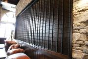 Firebirds' large wine rack on a dining wall awaits its vino. Cushions, still in packaging, rest on a leather bench seat below.