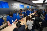 Employees ring up customers during the launch of the Apple Inc. iPhone 5c and 5s at the company's store in New York on Friday, Sept. 20.