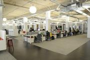 Most employees work at long rows of desks in a large open space.