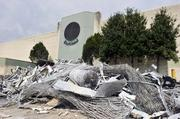 Scrap metal in a pile outside the main entrance, the day after the iconic sun logo was removed