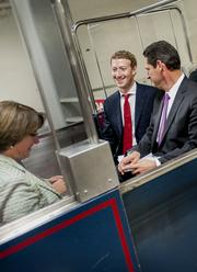 Mark Zuckerberg, founder and chief executive officer of Facebook Inc., center, rides on the Senate subway with Senator Amy Klobuchar, D-Minn., following a meeting with members of the Senate Committee on Commerce, Science and Transportation in Washington, D.C. on Thursday, Sept. 19, 2013.