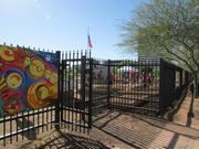 One of the entrances to PHX Renews. The fence surrounding the 15 acres is decorated with mural panels made by community members.