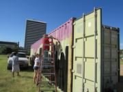 Students paint a city nightscape on a storage container that will be used to store supplies.