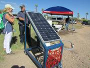 Dr. Ed Franklin, a professor in the Department of Agricultural Education at the University of Arizona, explains to a passerby how a solar-powered water pump operates. Franklin works with farmers in rural areas to develop alternative energy uses.