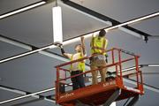 Electricians from Redwood Electric install lighting fixtures in the ballroom at the San Jose McEnery Convention Center. The ceilings in the new ballroom are 30 feet high.