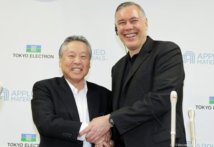 """Applied Materials Inc. CEO Gary Dickerson, right, shakes hands with Tetsuro """"Terry"""" Higashi, chairman of Tokyo Electron Ltd., during a news conference in Tokyo on Sept. 24. Applied Materials is acquiring Tokyo Electron and plans to cut costs amid a slump in demand for semiconductors."""