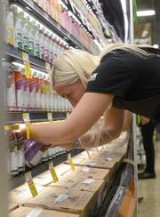 Whole Foods Education and Development Lead Nicole Kiley Feidt organizes an endcap at the grocer's new downtown Minneapolis store.