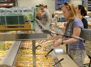 Karen Kaphingst, who lives nearby, grabs lunch from the salad bar. She's deputy director of healthy eating research at the University of Minnesota.