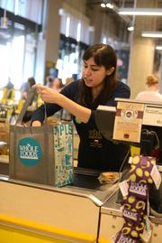 Customer service supervisor Diane Garcia packs groceries in one of the bags given to customers during the downtown Minneapolis Whole Foods store's grand opening.