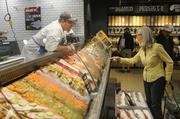 Sam Kolupailo helps a Whole Foods guest in the seafood department.